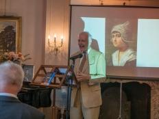 Coen Schimmelpenninck van der Oije achter het spreekgestoelte met op de achtergrond schilderij Volendams meisje